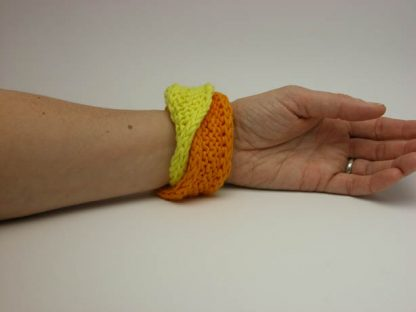 Hand knit double mobius bracelet in buttercup and mango fool cotton on wrist by Kate Wilcox-Leigh