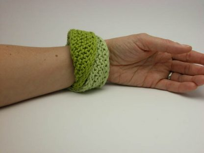 Hand knit double mobius bracelet in celery and gooseberry cotton on wrist by Kate Wilcox-Leigh