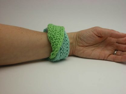 Hand knit double mobius bracelet in seafarer and mojitto cotton on wrist by Kate Wilcox-Leigh