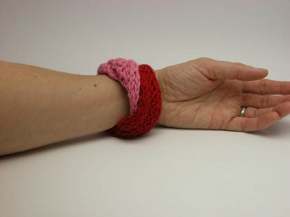Hand knit double mobius bracelet in slick and rosso cotton on wrist by Kate Wilcox-Leigh