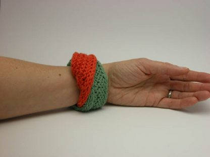 Hand knit double mobius bracelet in slippery and flamel cotton on wrist by Kate Wilcox-Leigh