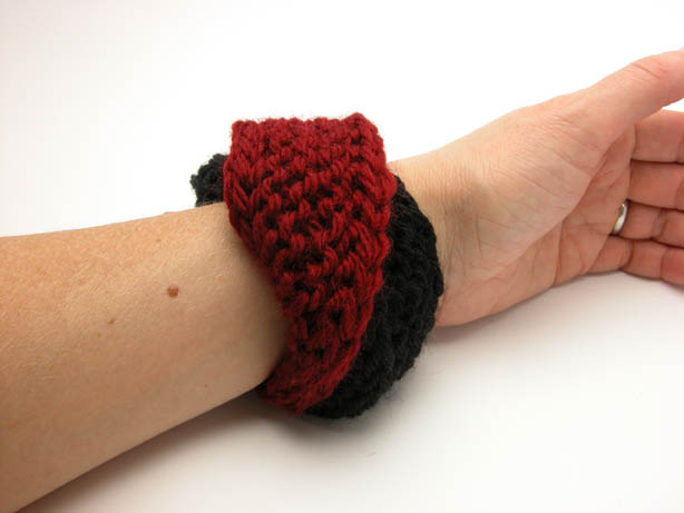 Hand knit double mobius bracelet in burgundy and black wool on wrist by Kate Wilcox-Leigh