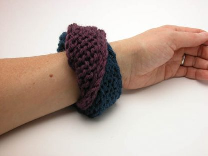 Hand knit double mobius bracelet in eggeplant and gobel in blue wool on wrist by Kate Wilcox-Leigh