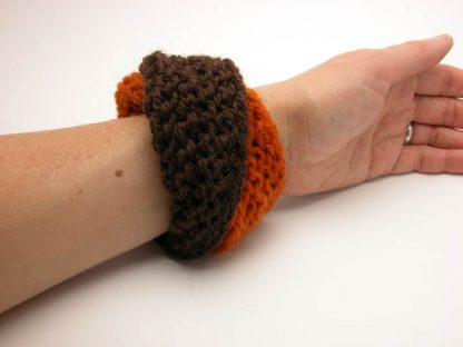 Hand knit double mobius bracelet in pumpkin and brown wool on wrist by Kate Wilcox-Leigh